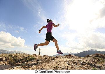 healthy young woman trail runner running on beautiful mountain peak