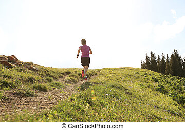 healthy young woman trail runner running on beautiful...