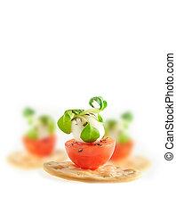 Cherry tomato, mozzarella chess and basil leaf on cracker isolated on white