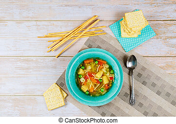 Healty soup with vegetables, crackers and bread sticks.