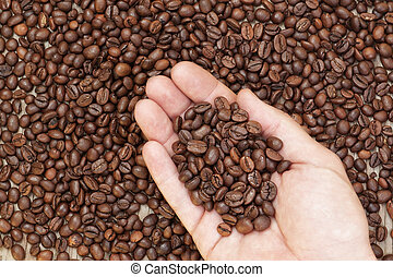 Heap coffee beans in the palm of a man. On the background coffee.