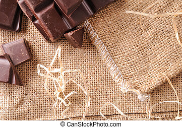 Heap of artisan portions chocolate on burlap top view