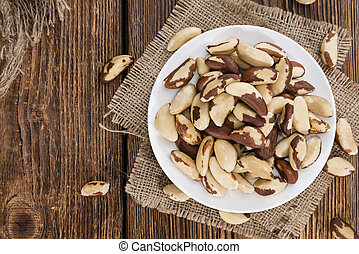Heap of Brazil Nuts (close-up shot) on wooden background