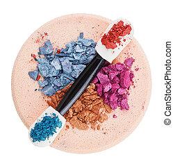 Heap of broken multicolor eyeshadow over makeup sponge, isolated on white macro