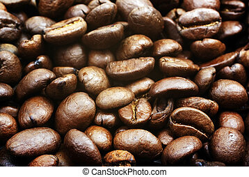 Heap of brown roasted coffee beans close up photo as background or backdrop.