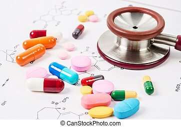 Heap of color pills and tablets with stethoscope medical.