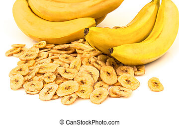 Heap of dried banana chips with yellow banana bunch