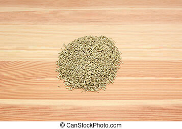 Heap of dried fennel seeds on wood