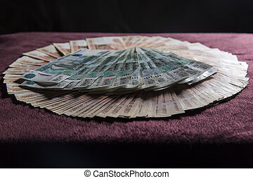 Heap of five thousand russian rubles banknotes, stack on red velvet