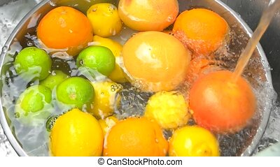 Heap of fresh citrus fruits under tap water, top view. Water...
