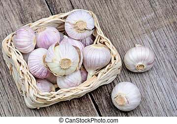 Heap of fresh garlic in a wicker basket on rustic table