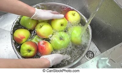 Heap of fresh green apples in water. Top view hands washing...