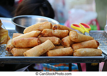 Heap of fried spring rolls place on the stainless grill and tray.