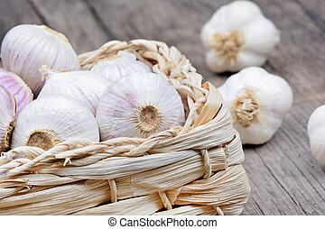 Heap of garlic in a wicker basket on table