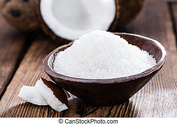 Heap of Grated Coconut (close-up shot) on wooden background