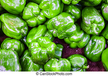 heap of green capsicum in retail vegetable super market for sale