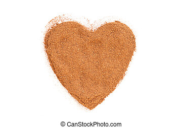 Heap of ground Cinnamon isolated in heart shape on white...