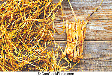 Heap of homemade bread sticks on wooden table with straw
