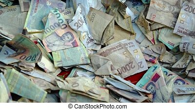 Pile of Indonesian bank notes in various denominations, alternately folded or wadded, given as religious offerings at a Hindu temple in Bali. 4k footage