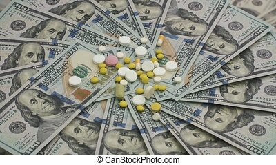 Heap of mixed pills rotating on money - healthcare cost concept