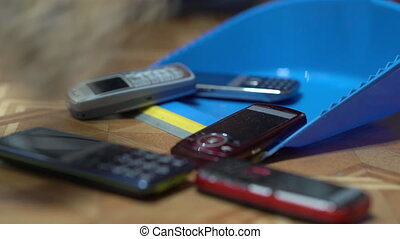 Heap of old mobile phones on dustpan - Old mobile phones...