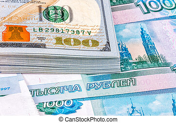 Heap of one hundred american dollar banknotes over russian roubles