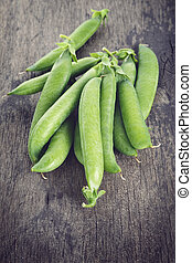 heap of pea pods on old wood table