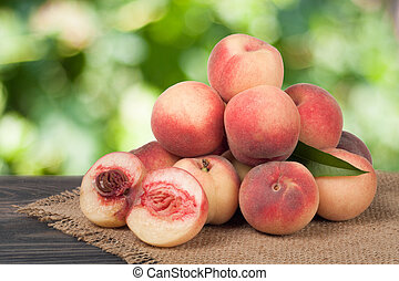 heap of peaches on a wooden table with blurred background