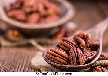 Heap of Pecan Nuts (selective focus) on an old wooden table