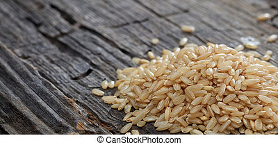 Heap of raw brown rice on an old wooden surface