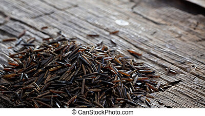 Heap of raw wild rice on an old wooden table