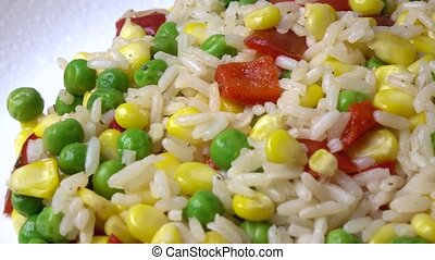 Heap of rice, corn, peas and red sweet pepper on the plate, 4K dolly shot