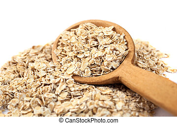 Heap of rolled oats with wooden spoon on white