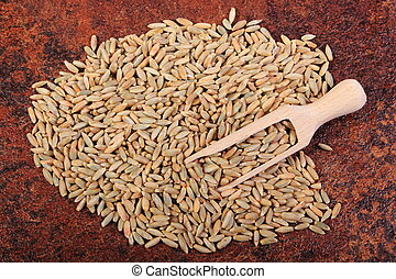 Heap of rye grain with wooden spoon