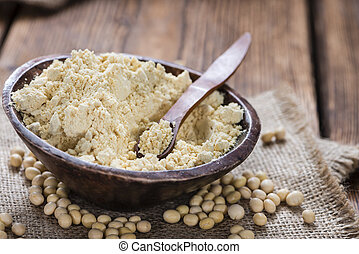 Heap of Soy Flour (close-up shot) on rustic wooden table