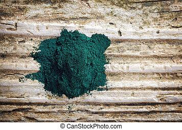 heap of spirulina algae powder on wooden background, top...