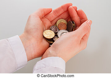 Heap of various coins in female hands.
