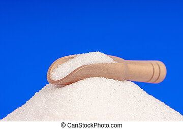 Heap of white sugar with a wooden spoon on a blue background