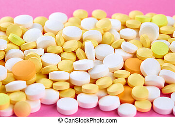 Heap of white yellow and orange pills on pink background