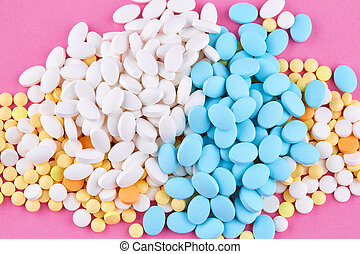 Heap of white yellow blue and orange pills on pink background