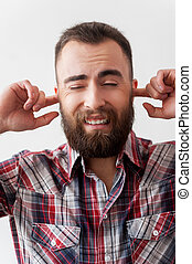 Hear no evil. Handsome young bearded man making a face and covering ears by fingers while standing isolated on grey background