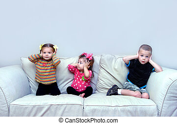 Hear no Evil - Three children sit on a couch in their home. ...