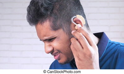 Hearing aid concept, a young man with hearing problems