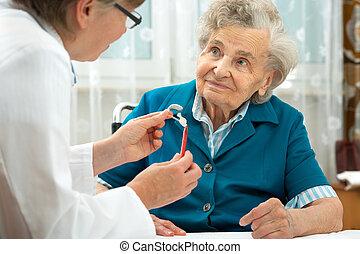 Hearing Aid - Deaf senior woman during a hearing test