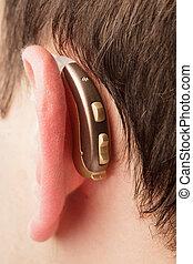 Hearing aid on the man's ear closeup