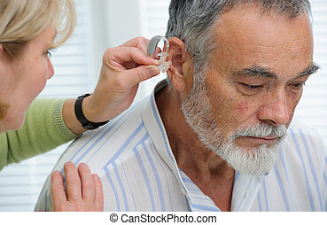 Hearing Aid - Doctor inserting hearing aid in senior's ear