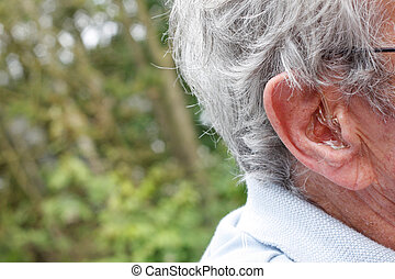 Hearing device - An older man with a hearing device