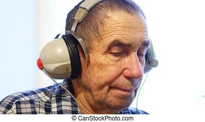 Hearing test. Man with headsets listen to a noise....