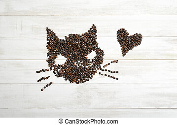 Heart and cat from coffee beans on wooden surface in top view.