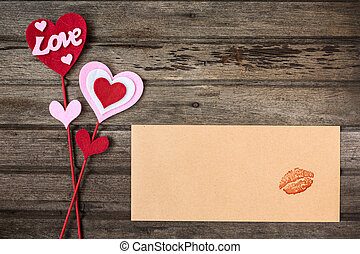 """""""Heart"""" and """"Love"""" valentine decoration and brown envelope with print of red kiss on wooden background, top view"""
